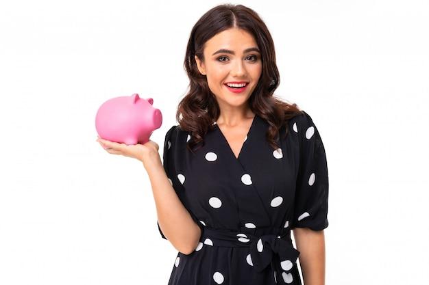La giovane ragazza caucasica con il sorriso delizioso, in vestito in bianco e nero in piselli tiene un salvadanaio rosa del maiale, immagine isolata su bianco