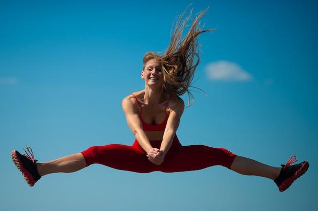 La giovane ragazza caucasica esegue lo spago che salta sul backround del cielo,