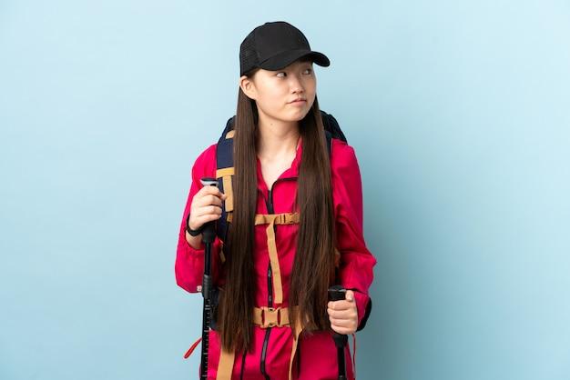 La giovane ragazza cinese con i pali di trekking e dello zaino sopra la parete blu isolata che fa i dubbi gesturing lo sguardo laterale