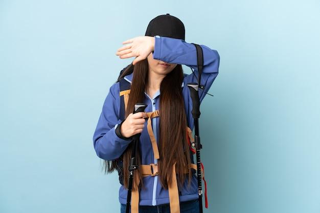 La giovane ragazza cinese con lo zaino ed i pali di trekking sopra la copertura blu isolata osserva a mano