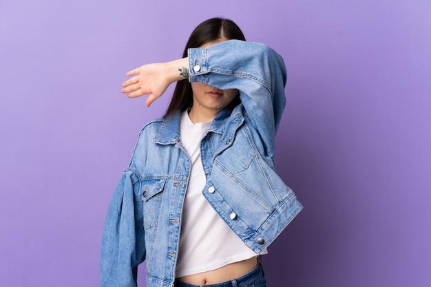 La giovane ragazza cinese sopra il rivestimento viola isolato della parete osserva a mano