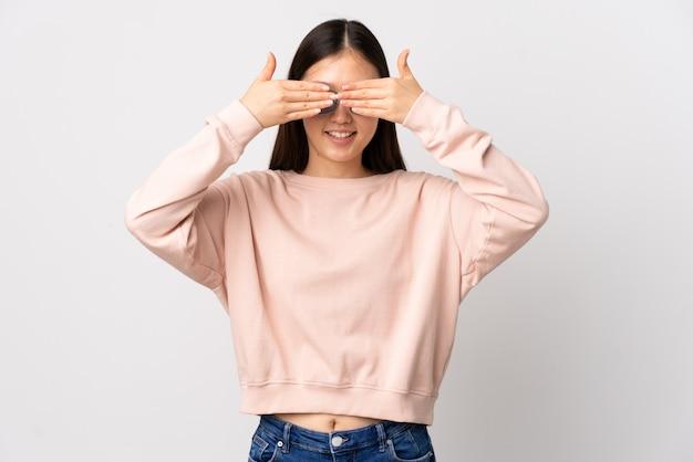 La giovane ragazza cinese sopra la copertura bianca isolata osserva a mano e sorridendo