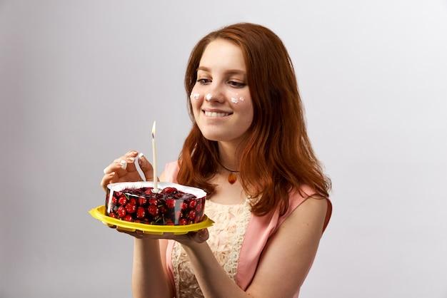 La giovane ragazza dai capelli rossi attraente che tiene una torta con la candela e fa un desiderio per il compleanno. la sua faccia coperta di crema dalla torta e dai dolci.