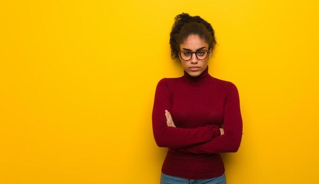 La giovane ragazza dell'afroamericano nero con l'incrocio degli occhi azzurri arma rilassato