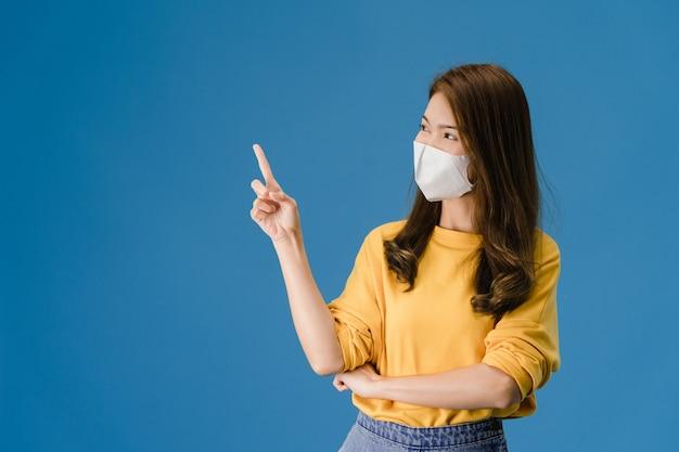 La giovane ragazza dell'asia che indossa la mascherina medica mostra qualcosa nello spazio vuoto con vestito in panno casuale e che guarda l'obbiettivo isolato su priorità bassa blu. allontanamento sociale, quarantena per il virus corona.