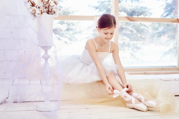 La giovane ragazza della ballerina sta preparando per un balletto