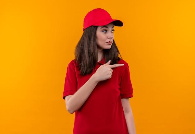 La giovane ragazza di consegna che porta la maglietta rossa nel cappuccio rosso punta un dito a lato su fondo giallo isolato
