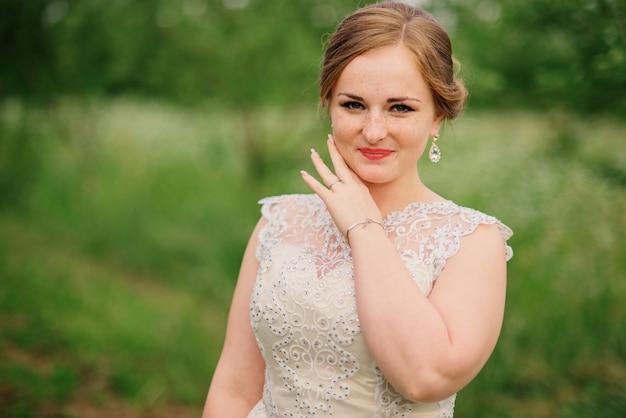 La giovane ragazza di peso eccessivo al vestito beige ha proposto il giardino della sorgente della priorità bassa.