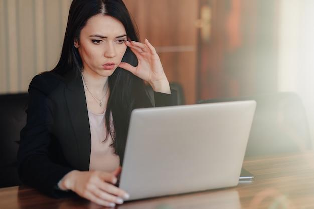 La giovane ragazza emozionale attraente in vestiti di stile di affari si siede ad uno scrittorio su un computer portatile e su un telefono nell'ufficio o nella sala