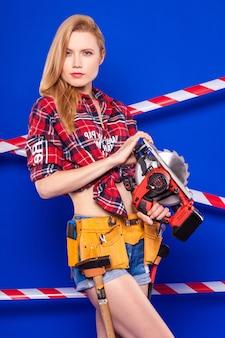 La giovane ragazza esile del costruttore in camicia a quadretti rossa, cintura del costruttore, shorts di jeans e snickers tiene la sega circolare
