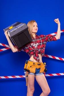 La giovane ragazza esile del costruttore in camicia chechered rossa, cinghia del costruttore, shorts di jeans e snickers tiene la cassetta portautensili