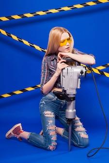 La giovane ragazza graziosa del costruttore in camicia a quadretti, jeans e vetri tiene il perforatore