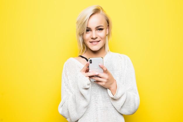 La giovane ragazza graziosa della donna della signora in maglione bianco utilizza lo smartphone su colore giallo
