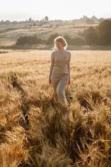 La giovane ragazza graziosa felice in vestito giallo cammina al campo delle orecchie nei raggi del sol levante