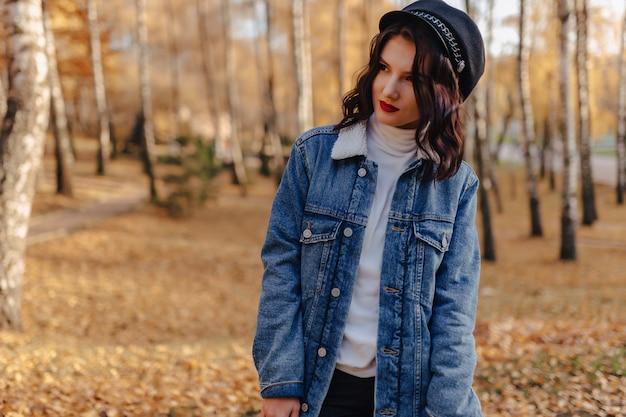 La giovane ragazza graziosa in un cappotto del denim cammina nella città di autunno