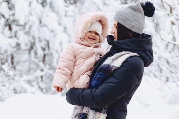 La giovane ragazza graziosa tiene il piccolo bambino sulle sue mani nell'inverno