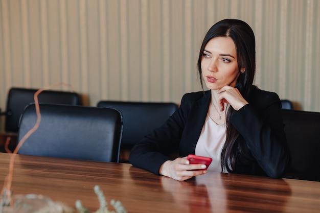 La giovane ragazza impressionabile attraente in vestiti di stile di affari che si siedono allo scrittorio con il telefono