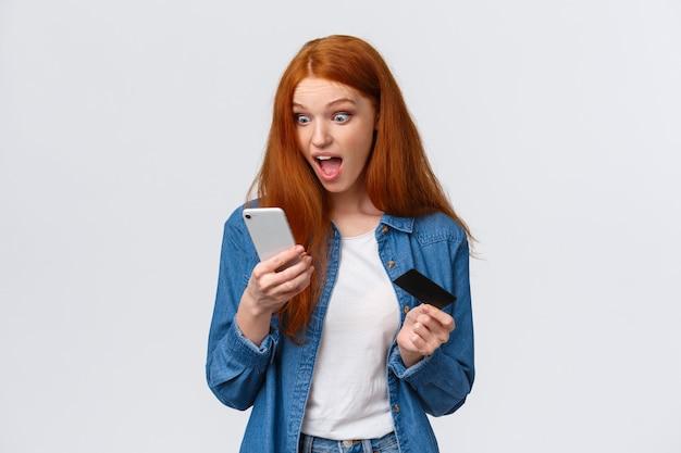 La giovane ragazza rossa eccitata e scioccata si affretta a comprare il vestito con uno sconto eccezionale, fissando lo schermo dello smartphone colpito e sorpreso, tenendo il telefono cellulare e la carta di credito,