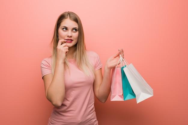 La giovane ragazza russa graziosa ha rilassato il pensiero a qualcosa che esamina uno spazio della copia. lei è in possesso di una borsa della spesa.