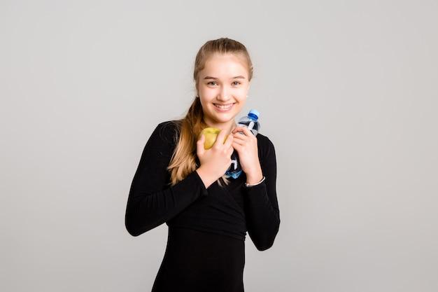 La giovane ragazza snella tiene una mela e una bottiglia di acqua. uno stile di vita sano
