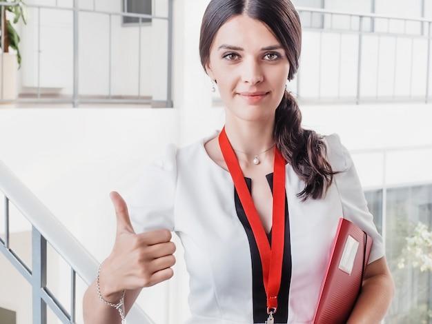 La giovane ragazza sorridente fatta il riuscito lavoro mostra il grande pollice di gesto.