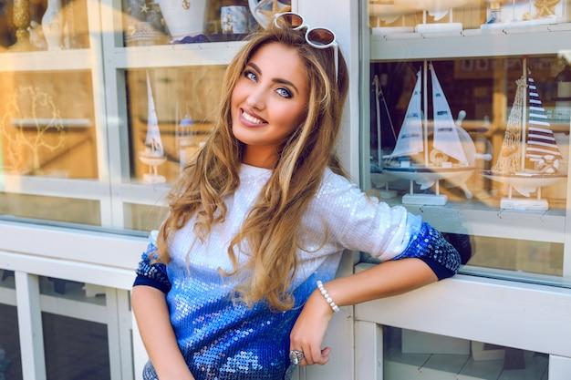 La giovane ragazza sorridente graziosa che posa vicino al negozio di souvenir con barche e merci dei marinai, indossa un maglione ombre, ha trucco naturale e soffice acconciatura arricciata. buona giornata e shopping.