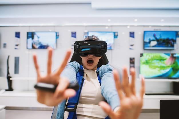 La giovane ragazza spaventata sta usando il sistema vr e viene spaventata dal gioco spaventoso in un luminoso negozio di tecnologia.
