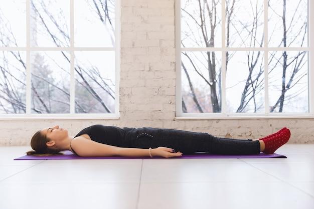 La giovane ragazza sportiva di yoga del beaute in asana di shavasana nella posa di resto. lunghezza intera