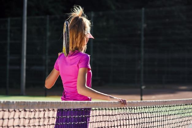 La giovane ragazza sportiva ha vestito gli abiti sportivi rosa con la racchetta sulla spalla sta vicino alla rete sul campo da tennis all'aperto.
