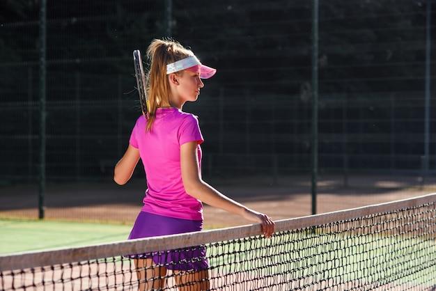 La giovane ragazza sportiva sveglia vestita con abiti sportivi rosa con la racchetta sulla spalla sta vicino alla rete sul campo da tennis all'aperto.