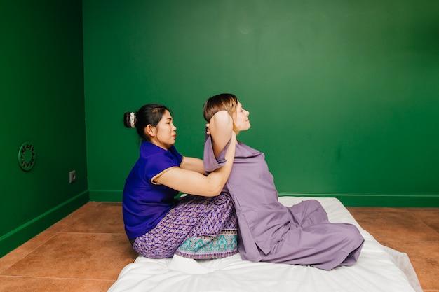La giovane ragazza tailandese del lavoratore del massaggiatore in costume esotico asiatico etnico fa e dimostra le diverse procedure tradizionali della stazione termale nella stanza verde di yoga di rilassamento