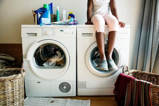 La giovane ragazza teenager che aspetta copre essere lavato dalla lavatrice