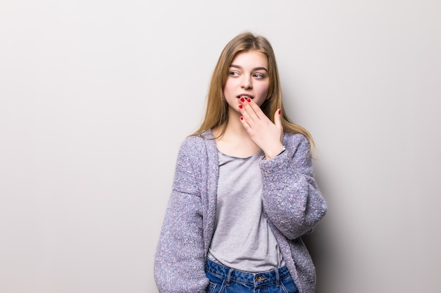 La giovane ragazza teenager copre la sua bocca nella mano di scossa su un muro grigio