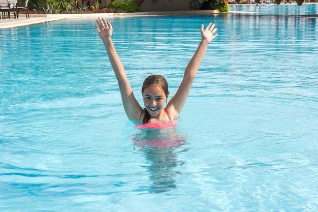 La giovane ragazza teenager nuota e si diverte nella piscina all'aperto