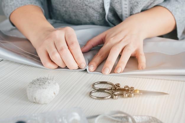 La giovane sarta fa vestiti che tagliano il tessuto