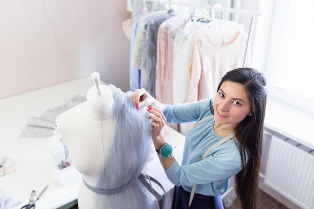 La giovane sarta indiana con lunghi capelli neri crea un nuovo vestito con piume su un manichino da cucito