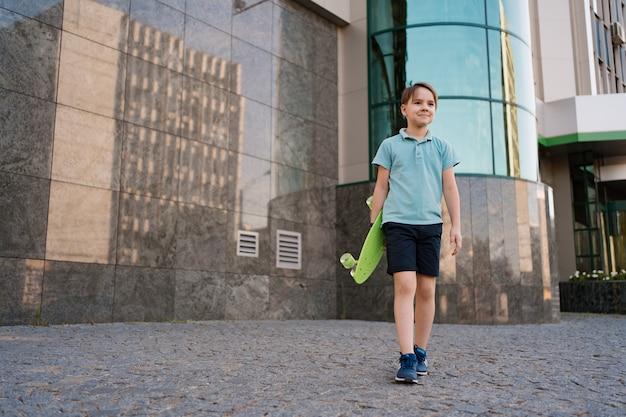La giovane scuola cool boy in abiti luminosi che cammina con penny board nelle mani