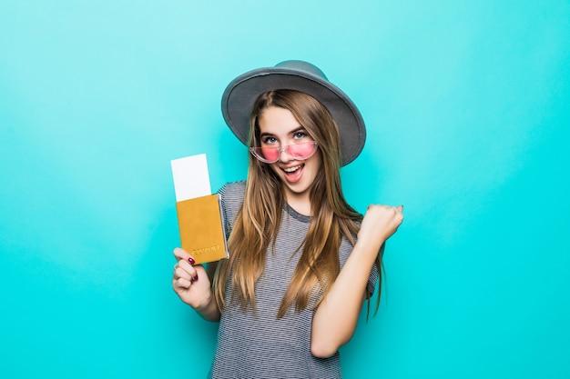 La giovane signora adolescente felice tiene i suoi documenti del passaporto con il biglietto nelle sue mani isolate sulla parete verde dello studio