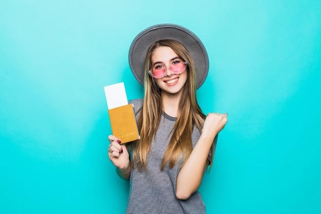 La giovane signora adolescente sorridente tiene i suoi documenti del passaporto con il biglietto nelle sue mani isolate sulla parete verde dello studio