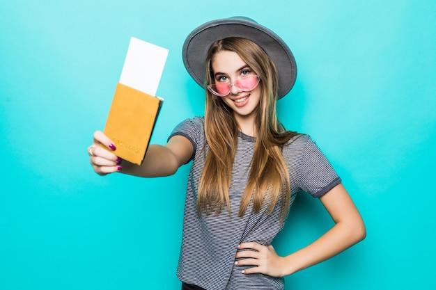 La giovane signora adolescente tiene i suoi documenti del passaporto con il biglietto nelle sue mani isolate sulla parete verde dello studio