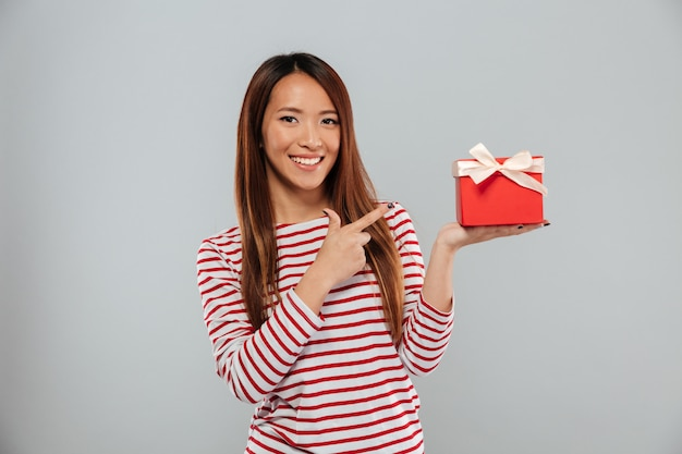 La giovane signora asiatica felice che sta la tenuta ha isolato il regalo e indicare della tenuta.