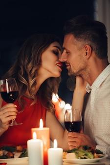 La giovane signora bacia il suo uomo splendido mentre cenano romantico