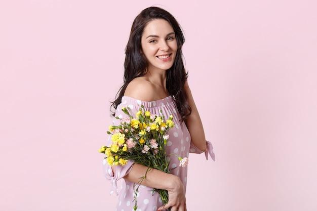La giovane signora castana ottimista positiva riceve i fiori sul compleanno, indossa un abito elegante a pois, sorride delicatamente, posa contro il muro rosa esprime felicità. donne e concetto di primavera.