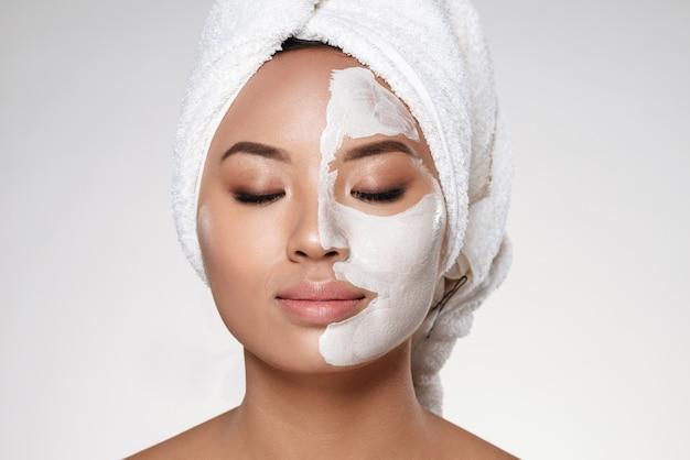 La giovane signora con l'asciugamano sulla testa ha messo la raschiatura sul suo viso