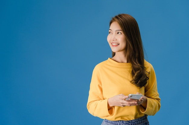 La giovane signora dell'asia che utilizza il telefono con l'espressione positiva, sorride ampiamente, vestita in abbigliamento casual sensazione di felicità e in piedi isolato su sfondo blu. la donna felice adorabile felice si rallegra del successo.
