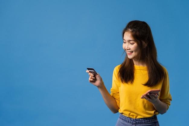 La giovane signora dell'asia che utilizza il telefono e la carta di credito con un'espressione positiva, sorride ampiamente, vestita in abbigliamento casual e sta isolata su fondo blu. la donna felice adorabile felice si rallegra del successo.