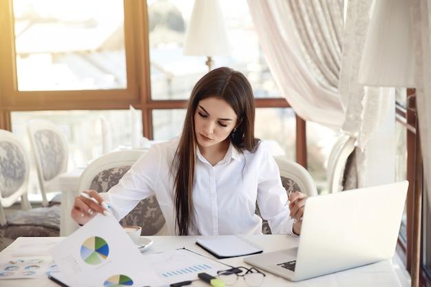 La giovane signora di affari del brunette sta analizzando i diagrammi e sta lavorando al computer portatile