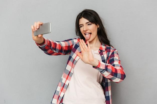 La giovane signora divertente sveglia fa il selfie dal telefono cellulare che ondeggia alla conversazione degli amici.