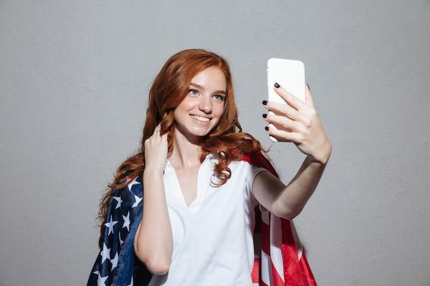 La giovane signora felice della testarossa con la bandiera di usa fa il selfie