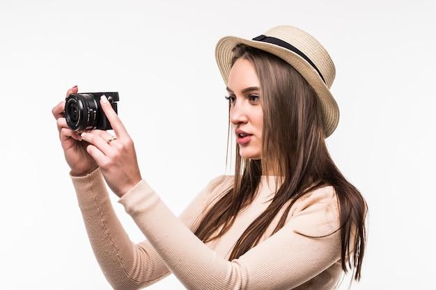 La giovane signora graziosa in maglietta e cappello luminosi fa la foto sulla retrocamera isolata su bianco